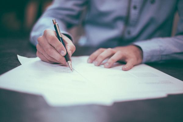 uzupełnianie dokumentów, mężczyzna podpisujący dokumenty